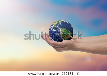 humans hand open palms gesture holding the world over blurred pastel sky backgrounds : human hand healing world life concept,ecology concept.environment day.Elements of this image furnished by NASA. - stock photo