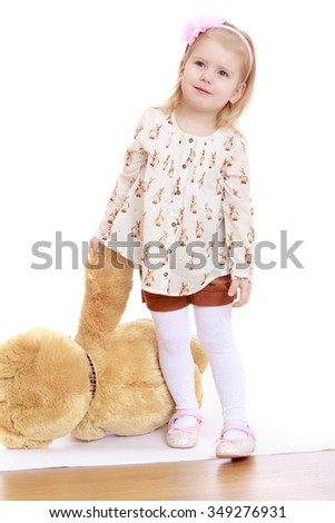 Humble, adorable, little, blond girl in a white shirt and brown shorts holding one hand behind his paw Teddy bear - Isolated on white background.The concept of a Happy childhood and child development - stock photo