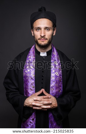 Humble catholic priest. Studio portrait on black background   - stock photo
