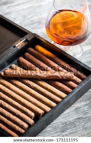 Humidor full of cigars and cognac - stock photo