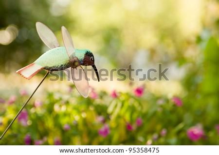 Hummingbird garden ornament in the garden - stock photo