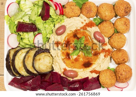 Hummus and falafel with fried vegetables and salad - stock photo