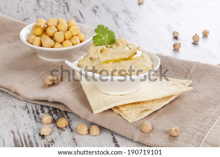 Hummus, chickpeas and pita bread on white wooden background. Culinary eastern cuisine. - stock photo