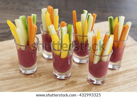 Hummus dip coloured with beetroot with vegetables. - stock photo