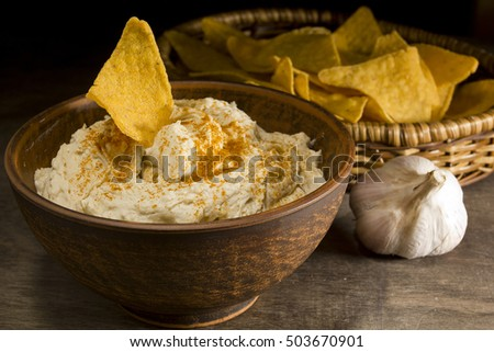 Hummus in an earthenware dish and garlic on a wooden background