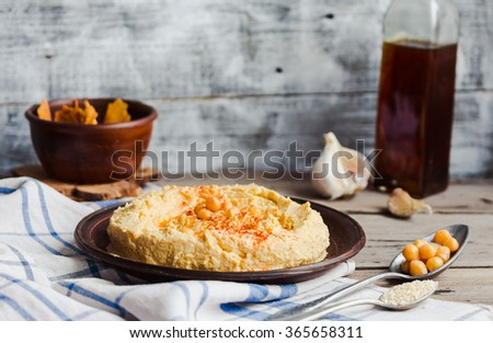 hummus of chickpeas, tahini paste and with paprika in a clay plate,vegan snack - stock photo