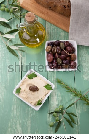 Hummus, olives, olive oil, and bread on a wooden table  - stock photo