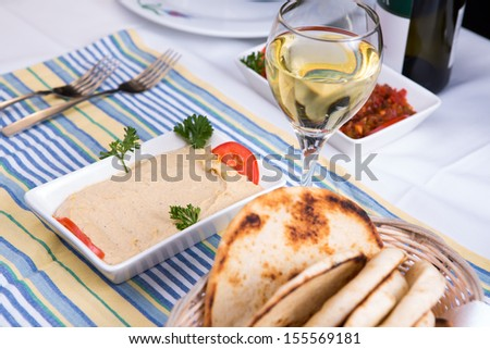 Hummus paired with white wine and pia breads and served on a blue striped cotton placement - stock photo