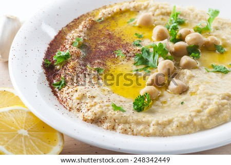 Hummus topped with olive oil, paprika and parsley. New version. - stock photo
