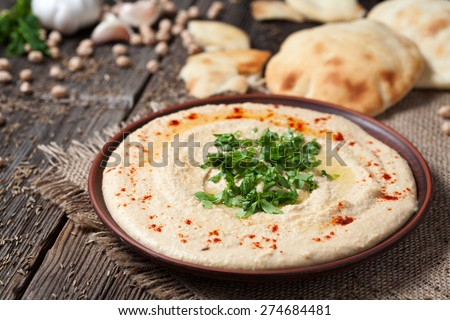 Hummus traditional Jewish creamy lunch salad with chickpeas, olive oil and paprika. Served with fresh backed pita bread - stock photo