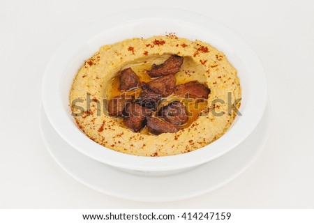 Hummus with braised meat and ground red pepper - stock photo