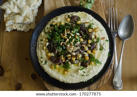 Hummus with lamb meat, chickpeas and toasted pine nuts - stock photo