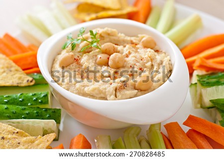 Hummus with vegetables on plate - stock photo