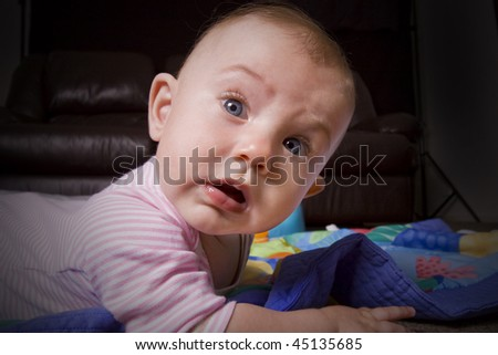 humorous close up of a little baby crawling on the floor - stock photo