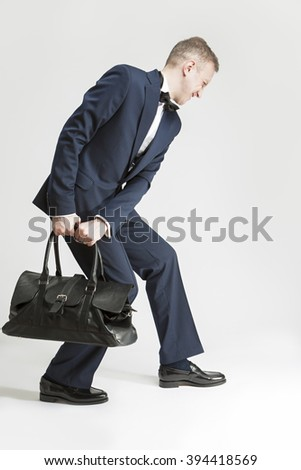 Humorous Concept and Ideas. Handsome Caucasian Man in Official Suit and Bow Tie Hauling Leather Long Bag.Vertical Shot