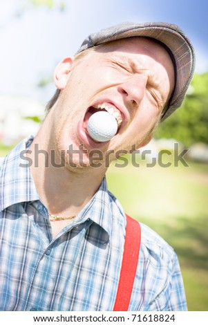 Humorous Head And Shoulders Portrait Of A Young Man's Reaction On A Golf Course Immediately After Catching A Flying Golf Ball In His Open Mouth - stock photo
