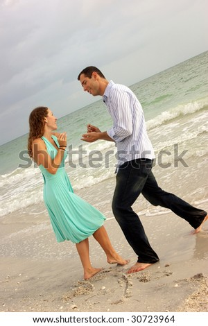 humorous image of beautiful young couple on beach pretending to propose on the beach. - stock photo