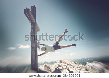 Humorous Image of Man Clinging to Summit Cross on Extremely Windy Day in Allgau Alps with View of Mountains in Background, on Sunny Day with Blue Sky - stock photo