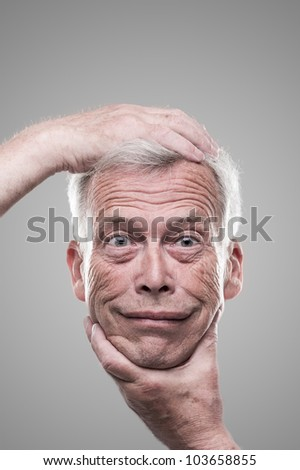Humorous macabre self portrait. Humorous macabre self portrait of a senior man holding up his own smiling face at arms length for an inspection on a grey studio background - stock photo