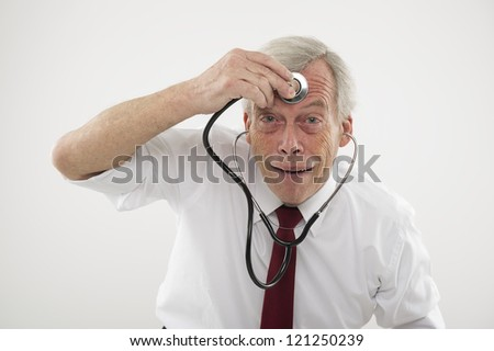 Humorous medical concept of a senior man pulling a comical face holding a stethosope to his forehead as though checking his brain function, intellect, wisdom or cognitive powers - stock photo