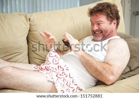 Humorous photo of a man in his underwear, using his cellphone to send a picture of his penis.   - stock photo