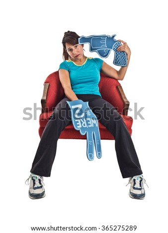 """Humorous photograph of a mixed race adult female sports fan with a foam finger declaring """"We're #2."""" The woman looks away from the camera while holding a foam gun (revolver) to her head. - stock photo"""