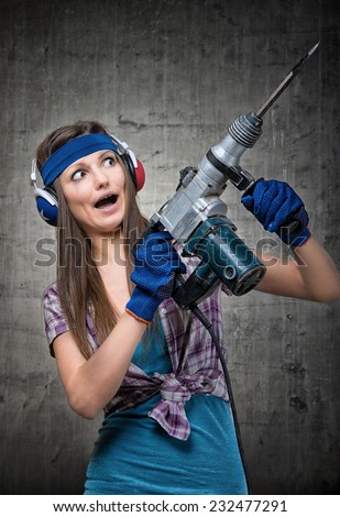 Humorous portrait of a housewife using a jackhammer to drill into wall - stock photo