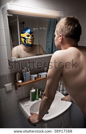 Humorous portrait of a man seeing him self as a wrestler in mirror. - stock photo