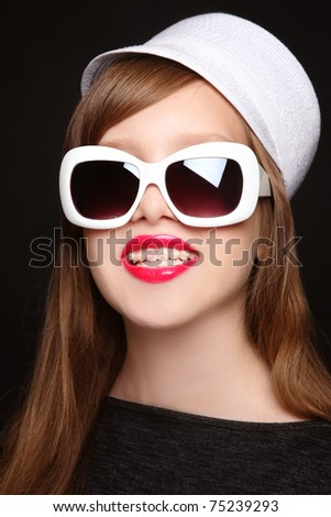 Humorous portrait of pretty glam smiling teen girl with dental braces