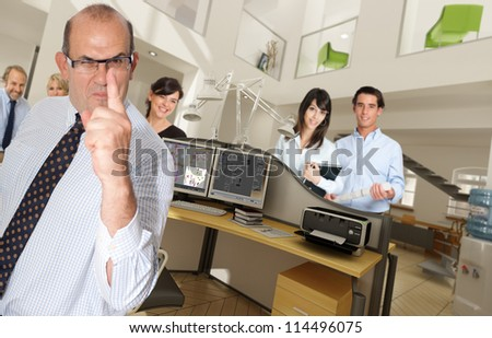 Humorous shot of a menacing business man in an office surrounded by smiling workers