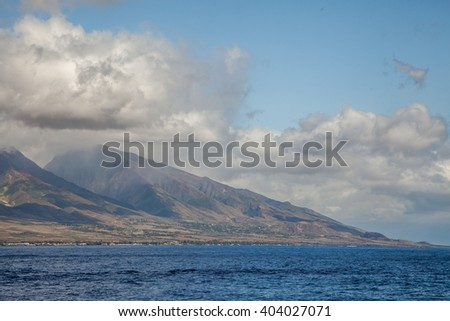 Humpback Whale Breach in front of blua sky with white clouds, Maui island, Hawaii - stock photo