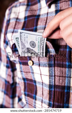 hundred american dollars in the pocket of shirt. cash money - stock photo