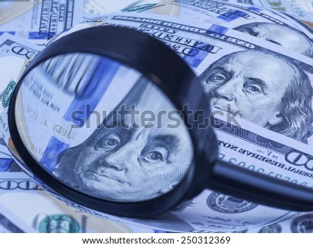 Hundred dollar banknotes under magnifying glass  - stock photo