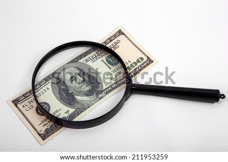 Hundred dollar bill under a magnifying glass  - stock photo