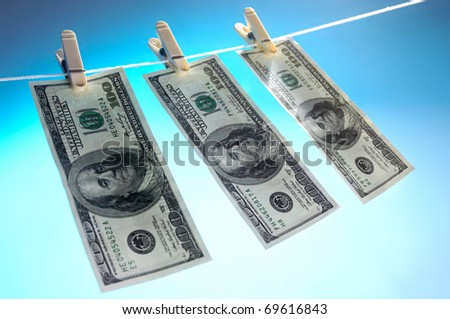 Hundred dollar bills drying on a clothes line isolated on blue sky background Money laundering concept - stock photo