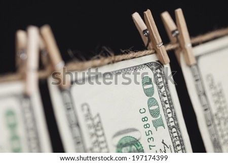 Hundred Dollar Bills Hanging From a Clothesline on a Dark Background. - stock photo