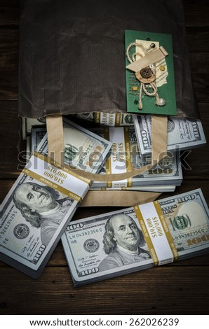 Hundred dollar bills in a gift bag coming out of a paper bag on old vintage wooden background. Greeting card, Birthday ecard, Birthday card - stock photo