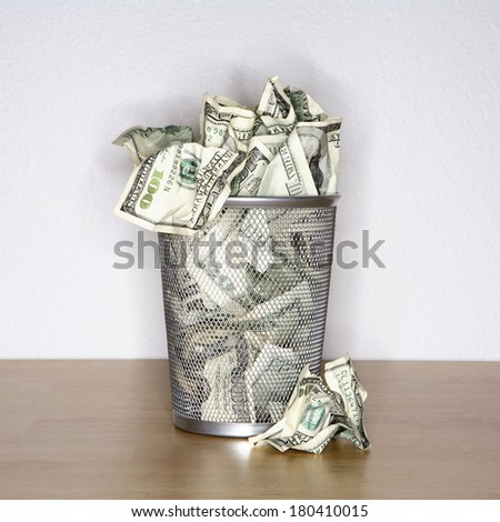 hundred dollar bills in trash bin  - stock photo