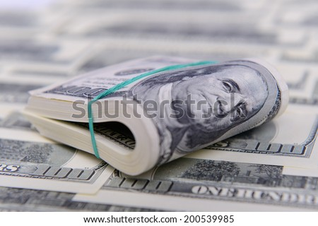 Hundred dollar bills rolled up with rubber band - stock photo