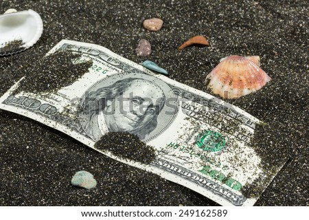 hundred dollars in the black sand with shells and pebbles - stock photo