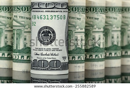 Hundred dollars over other bills - stock photo