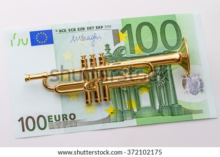 Hundred euro and a musical instrument trumpet. Abstract composition