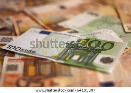 Hundred Euros on euros background shallow DOF - stock photo