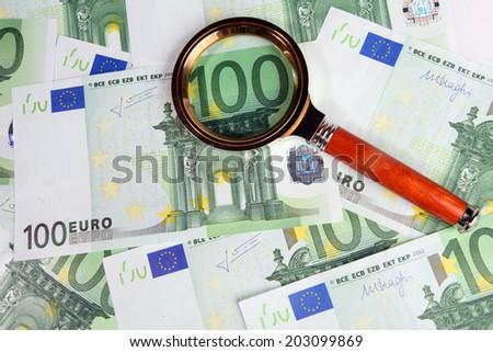 Hundred euros under magnifying glass - stock photo