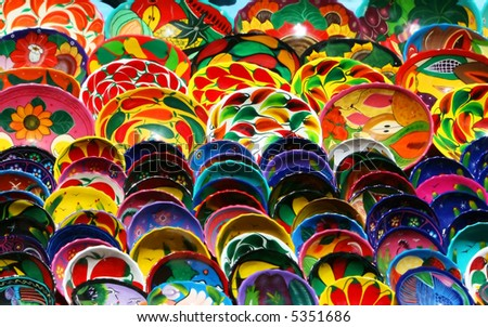 Hundred of handmade bowls are arranged neatly on tables in Chichen Itza Mexico. They are beautifully painted with vibrant colors and unique designs. - stock photo