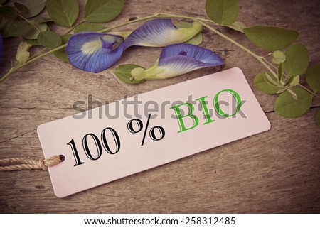 Hundred percent Bio inscription. Green and black inscription hundred percent Bio on blank tags on wooden table - stock photo