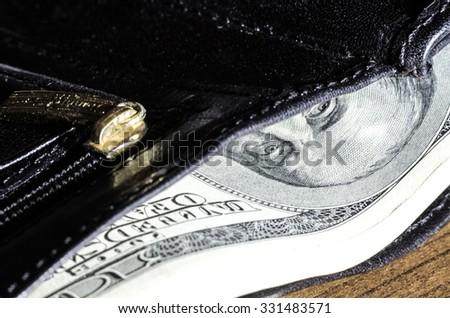 hundreds dollars in the wallet Benjamin Franklin eyes - stock photo