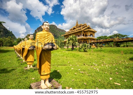 Hundreds of statues of Buddhist monks collecting alms surround beautiful myanmar temple - stock photo
