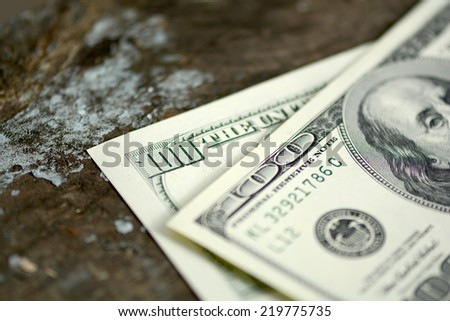 Hundreds of US dollars on old wooden plank - stock photo