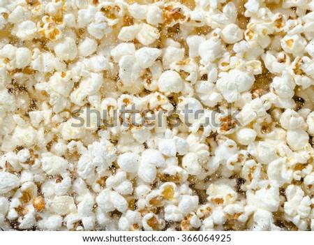 Hundreds popcorns background. Popcorns behind the glass of popcorn machine - stock photo